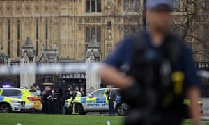 Armed police officer stands guard as emergency services gather at Carriage Gates entrance of UK parliament