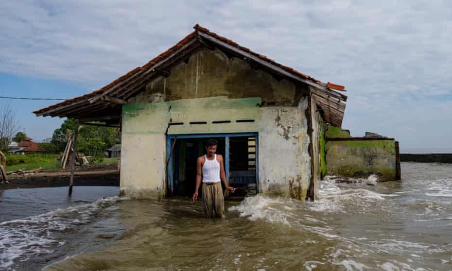 Pak Rasali stands outside his home damaged by exposure to the sea, which was several hundred meters further out just 10-12 years ago. May 28, 2021 in Pekalongan, Java, Indonesia.