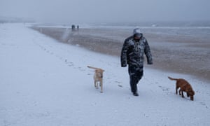 A dog walker leaves footprints in the snow on Whitley Bay beach