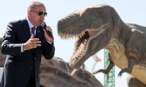 Turkish president Recep Tayyip Erdoğan delivers a speech next to a model dinosaur during the opening ceremony of a theme park.