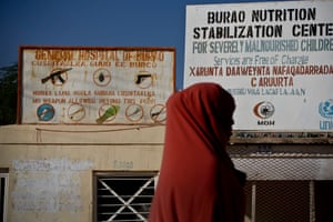 A woman walks past signs for the nutritional stabilisation unit in Burao – there is also a sign declaring that no weapons are allowed at Burao's hospital