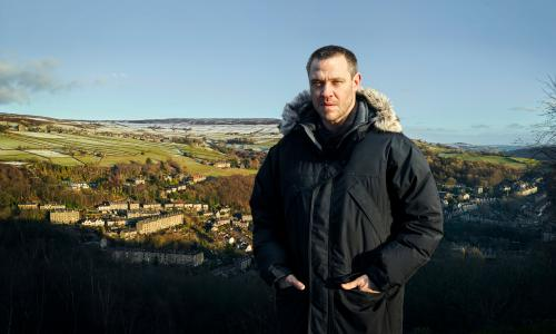 Will Young in a winter coat, a view over Hebden Bridge and surrounding hills behind him