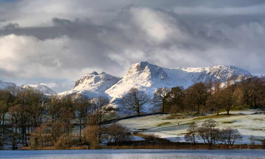 The snow capped Langdale Pikes in the Lake District National park, viewed across Loughrigg Tarn