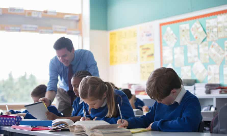 Male teacher assisting primary school children