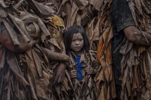 Devotees covered in mud and dried banana leaves take part in the Taong Putik festival in the village of Bibiclat.