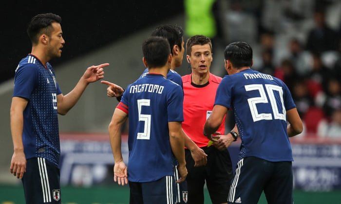 Japanese players argue with referee Benoit Bastien after he awarded Brazil a penalty in Friday's friendly, after checking with the video assistant referee.