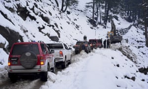 Vehicles wait for heavy machinery to clear a snow-choked road in Neelum Valley