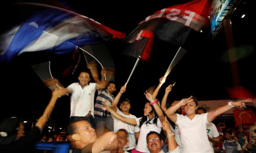 Supporters of Nicaragua's President Daniel Ortega and vice-presidential candidate, his wife, Rosario Murillo, wave a Nicaraguan flag and flags of the Sandinista National Liberation Front, or FSLN, while celebrating after preliminary results showed Ortega was on course for re-election.