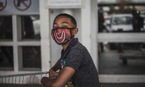 A boy wears a face mask as he queues outside a supermarket in Soweto, South Africa