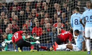 Manchester United's David de Gea saves a shot from Manchester City's Raheem Sterling.