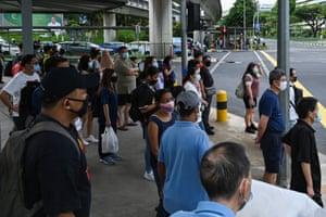 People wait at pedestrian crossing in Singapore on 23 June, 2020.