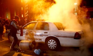 Police officers put out a fire in a police car after protesters set it on fire in front of City Hall in Ferguson