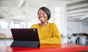 Africa-american woman smiling during a video call in office. Female professional using table pc for a video call in office.