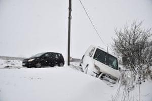 Motorists pass a van lying in a ditch in Belfast