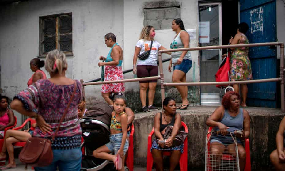 People wait to get food donations distributed by an NGO at the Cidade de Deus favela in Rio de Janeiro, Brazil, on 7 April.