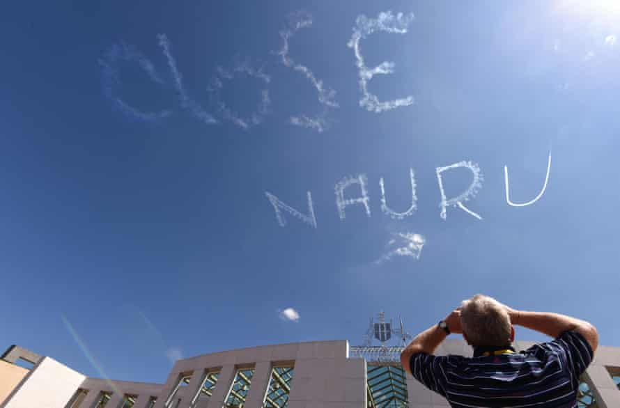 "A man watches as a plane skywrites ""CLOSE NAURU"" above Parliament House in Canberra."