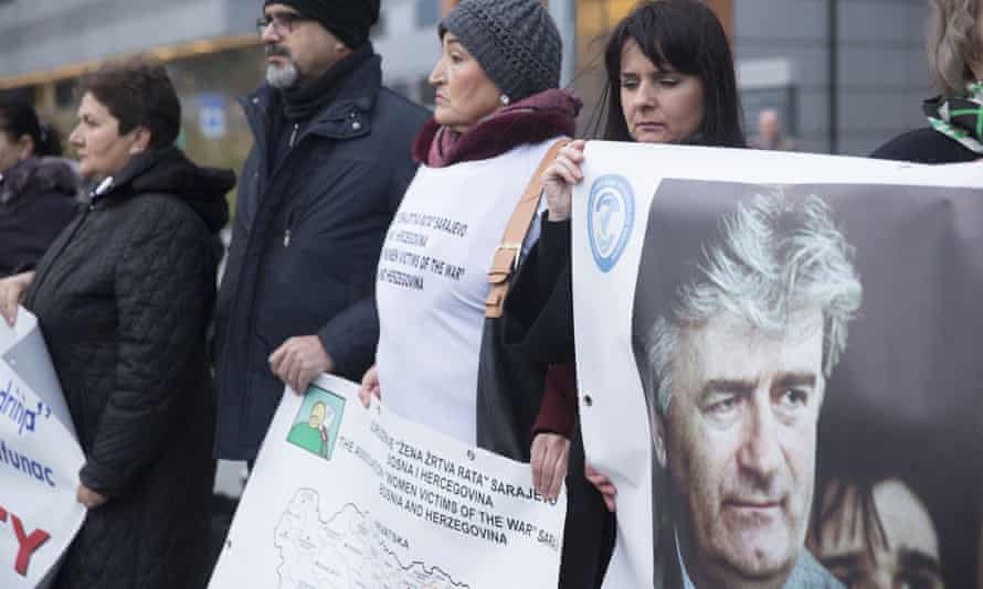 Protesters stand outside the court in The Hague with posters including one of Radovan Karadžić as they wait for the verdict on Ratko Mladic in November.