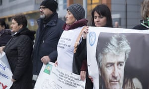 Protesters stand outside court on Wednesday holding posters including one of Radovan Karadzic, a Bosnian Serb former politician and convicted war criminal, as they wait for the verdict against Ratko Mladic