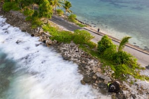 A woman stands at narrowest point of Fongafale island in Funafuti atoll