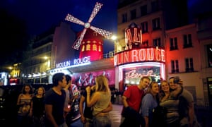 Tourists take a selfie in front of the Moulin Rouge cabaret in Paris.