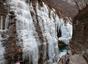 A tourist enjoying the scenery of icefall at Yuntai Mountain scenic spot in Jiaozuo, central China's Henan Province.