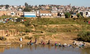 Women wash clothing in a polluted river in Madagascar's capital, Antananarivo