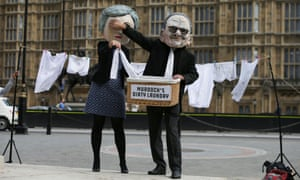Activists from Avaaz posing as Theresa May (left) and Rupert Murdoch protest against the proposed takeover of Sky by 21st Century Fox outside Westminster