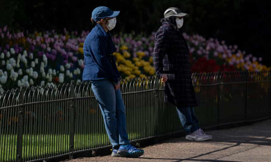Two people wearing faces mask in St James Park, London