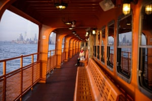 New York City, U.S. A lone commuter enjoys the sunset on the upper deck of the Staten Island Ferry