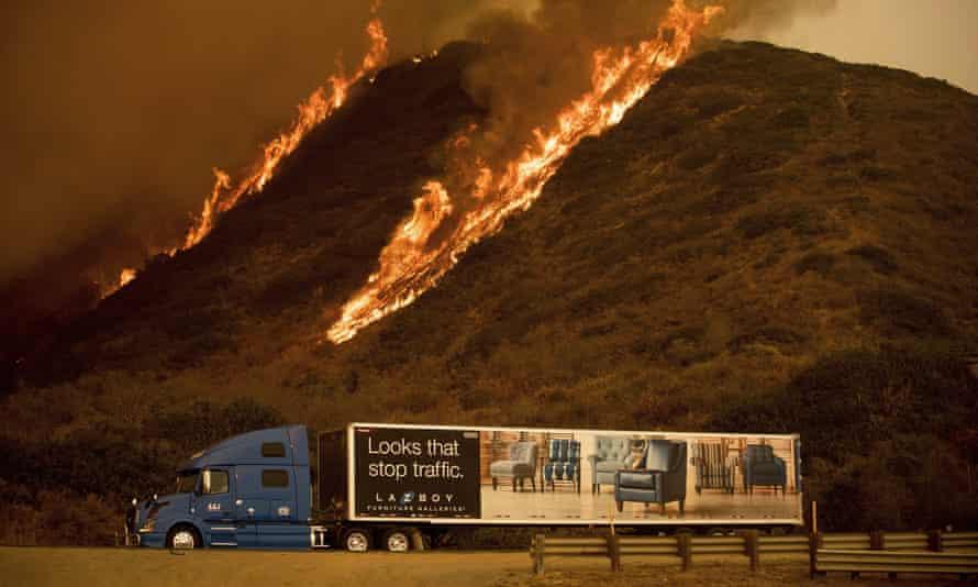 Flames burn on a hillside behind Highway 101 north of Ventura, California.