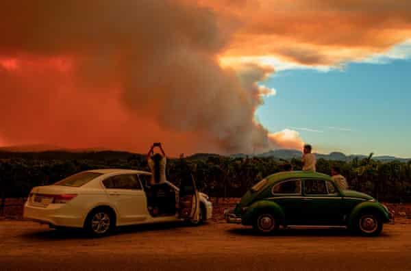 As pessoas assistem ao incêndio da Walbridge a partir de uma vinha em Healdsburg na quinta-feira.
