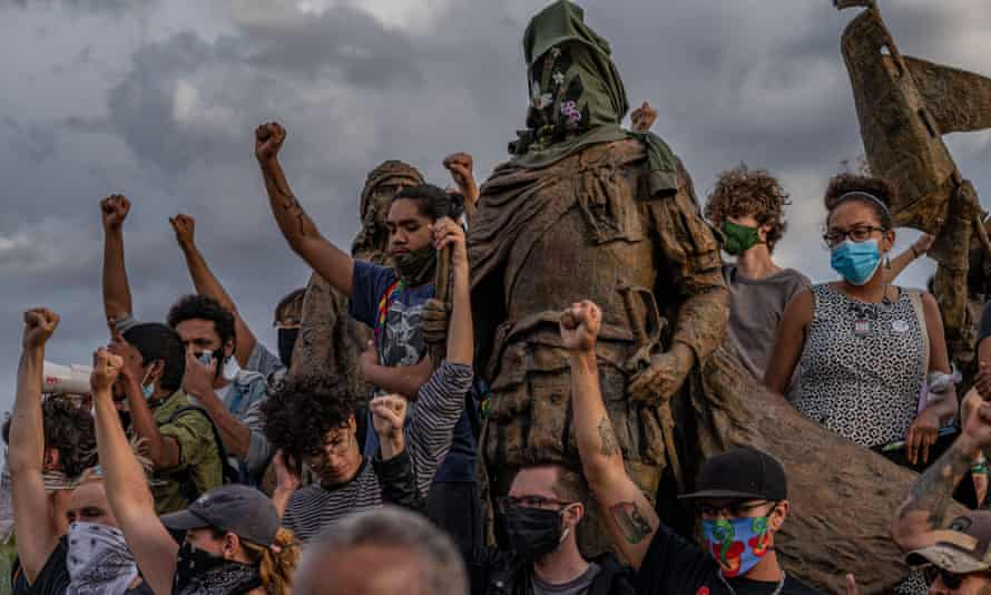 Protesters surround a statue of Juan De Oñate, known for ordering the massacre of 800 Indigenous people, in Rio Arriba county, New Mexico.