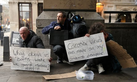 """A homeless man holds a sign reading """"What about us Boris - were we gunna isolate? Help!"""""""