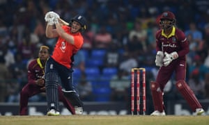 Eoin Morgan slogs for six runs in England's reply.