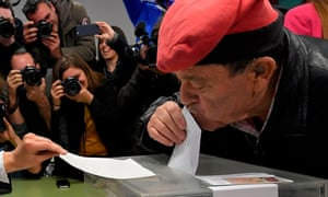 A man wearing a barretina, the traditional Catalan hat, kisses his ballot while voting in Barcelona.
