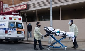 Paramedics transfer an elderly patient with Covid-19 symptoms into a hospital in Brooklyn, New York.