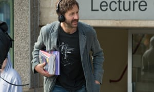 Chris O'Dowd outside a lecture theatre with headphones on in a black t-shirt and denim jacket, books under his arm, in Juliet, Naked.