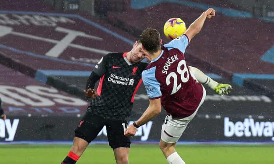 Jordan Henderson of Liverpool (left) clears the ball with his head while Tomas Soucek raises a foot to try and send it goalwards.