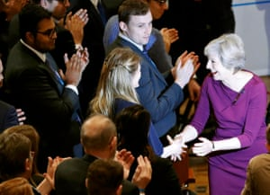 Theresa May shakes hands with delegates as she leaves the stage after giving her speech.