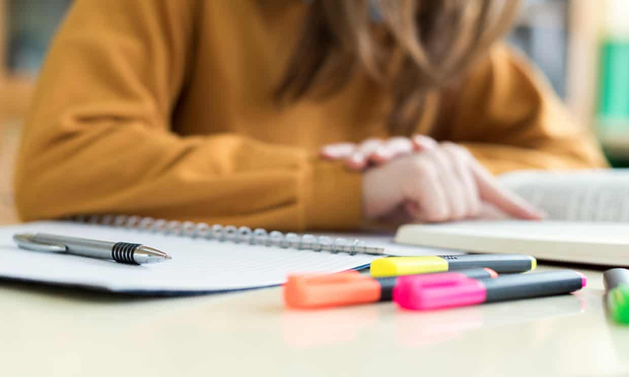 Young woman reading textbook, with notebook and highlighters on desk