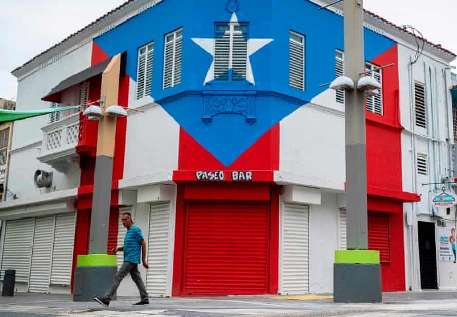 A man walks through a closed commercial area in San Juan