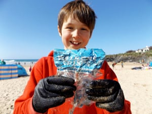 ten year old boy laurence miller holding a 1980s crisp packet he found on a beach in cornwall