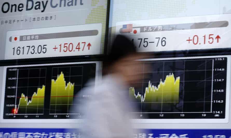 A man walks past a stocks board in Tokyo.