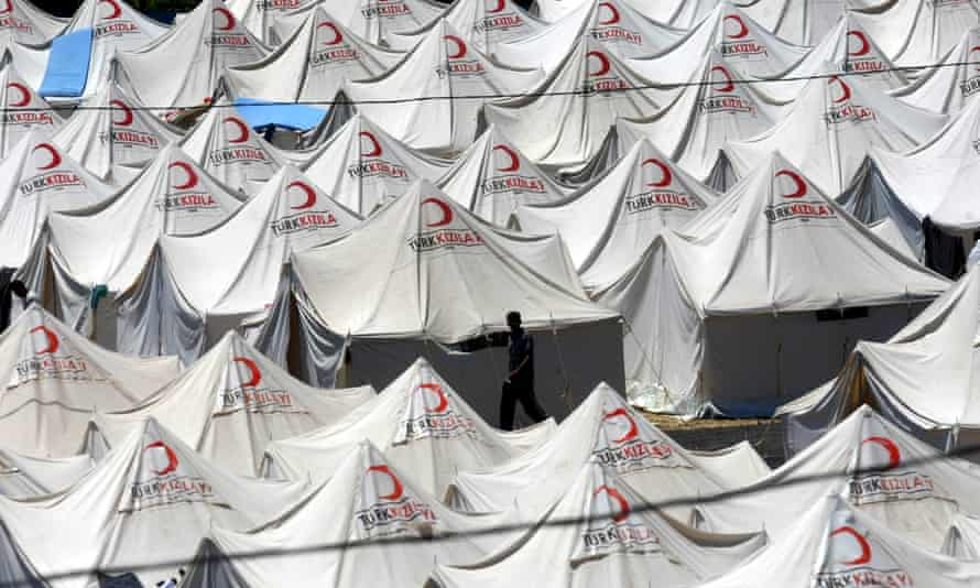 A Syrian refugee walks through rows of tents in a refugee camp in the Turkish border town of Yayladagi in June 2011.