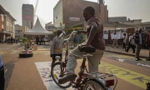 Street children borrow bikes and race each other down Luwum Street.