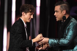 Robbie Williams presents the Aria award for best video to Troye Sivan (left).