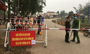 Police wearing masks guard a road checkpoint outside Son Loi in Vietnam