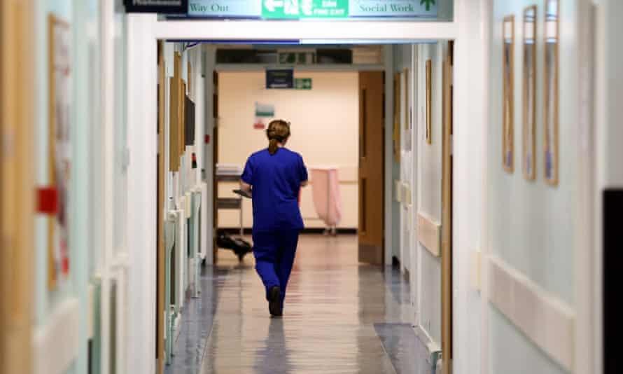 A nurse walks in a hospital corridor