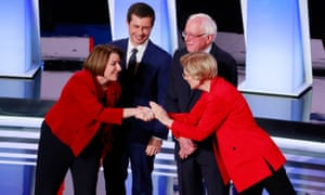 Amy Klobuchar (left) and Elizabeth Warren (right) greet each other at the beginning of the Detroit Democratic debate. Pete Butigigig and Bernie Sanders watch.
