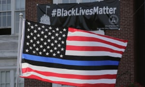 In a picture from July 2016, a flag with a blue and black stripes in support of law enforcement officers, flies at a protest in Somerville, Massachusetts.